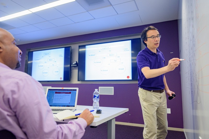 Xiao Fang, UD professor of management information systems, explains a new concept during one of five courses in a new collaboration between JPMC and the Lerner College.