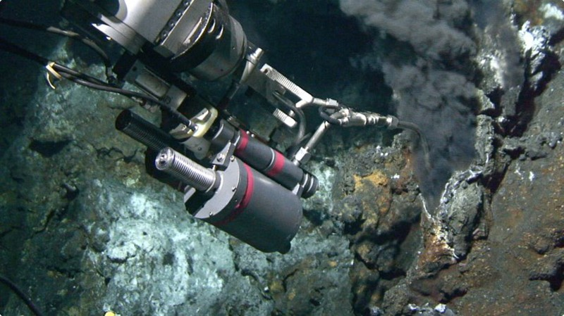 "Alvin, the undersea research vehicle, has a robotic arm that deploys a hydraulic fluid sampling device with a ""snorkel"" that sticks into the black smoker fluid."