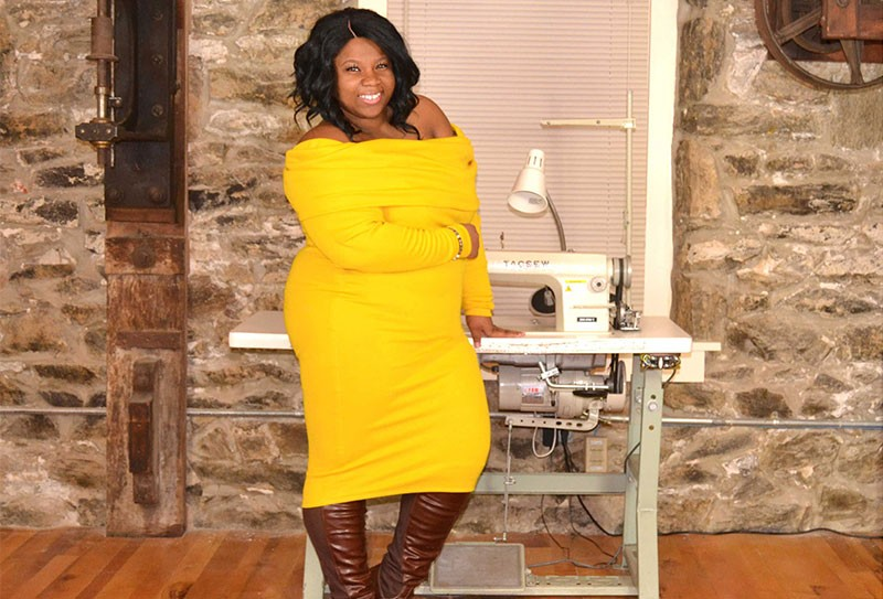 Alum Cha Cha Hudson stands with a sewing machine