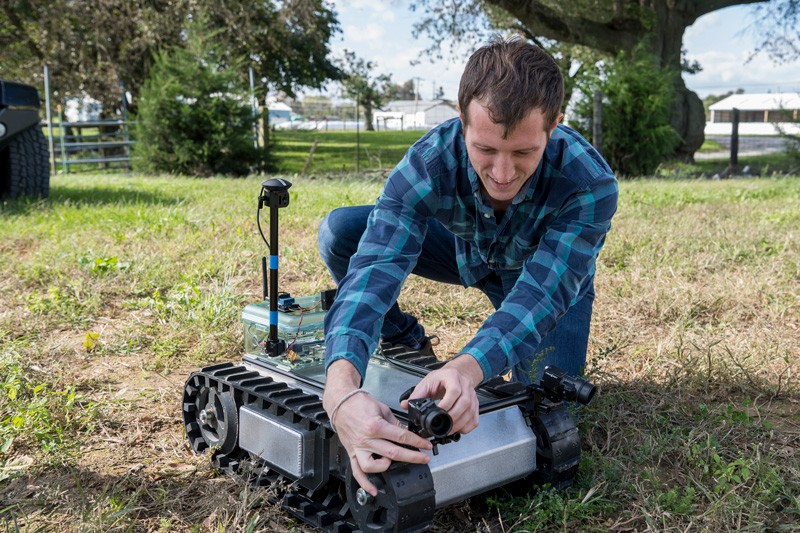 Adam Stager, a UD doctoral student in mechanical engineering, adjusts the ground robot before sending it into the field.