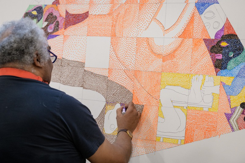 "Peter Williams fills in the outlines he's drawn for a piece titled ""Once We Built Pyramids,"" referring to the ancient Nubian Dynasty in Africa. He uses thousands of brightly colored dots, creating a different look from the traditional pointillist painting technique pioneered by 19th century artists such as Georges Seurat."