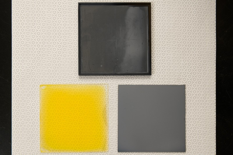 Overhead shot of the graphite susceptor (top), a nanocrystalline film-coated glass substrate (yellow) and a completed stack with the doped cadmium telluride film (gray).