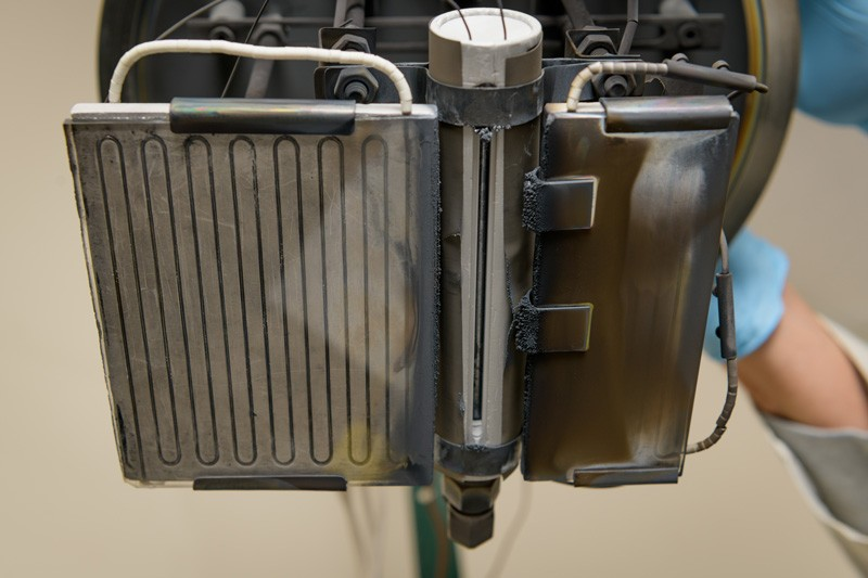 The exit slit and heater assembly of the IEC-designed and fabricated source head used to deliver doped cadmium telluride vapor to the substrate.