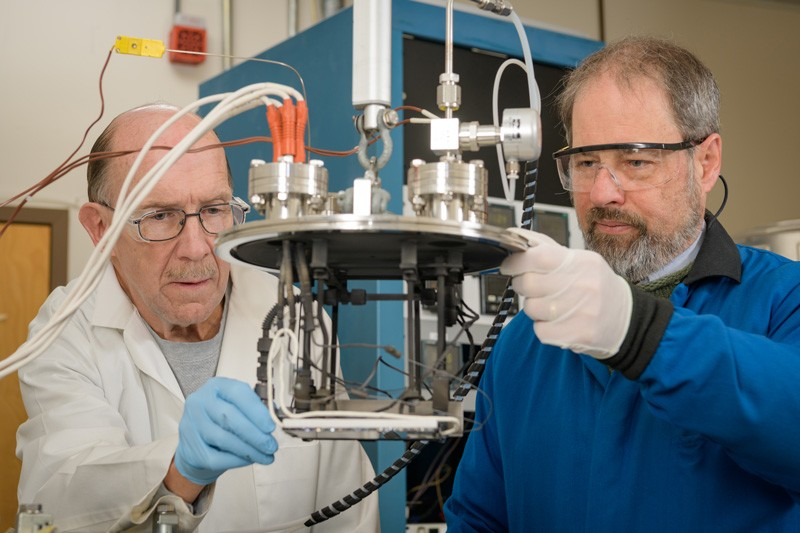IEC researchers Wayne Buchanan (left) and Brian McCandless (right) lowering the vapor source head into the vapor transport deposition system.