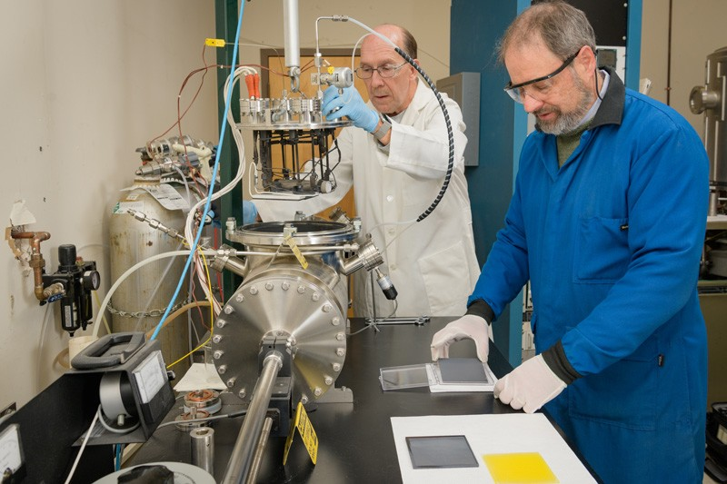 IEC researchers Wayne Buchanan (left) and Brian McCandless (right) prepare to load the vapor transport deposition system for a doped cadmium telluride film run. Buchanan is raising the source head out of the main chamber and McCandless is examining the previous film deposition (gray plate) and preparing to place the nanocrystalline film-coated glass substrate onto the graphite susceptor.