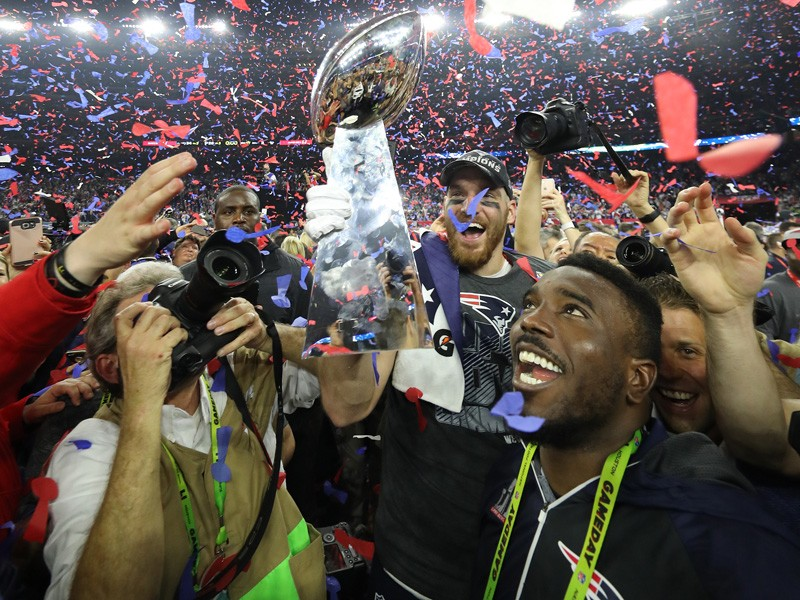 UD graduate Michael Akinbola, who is an athletic trainer/physical therapist for the New England Patriots, hoists the Vince Lombardi trophy following the Patriots' 34-28 OT victory over the Atlanta Falcons in Super Bowl 51.