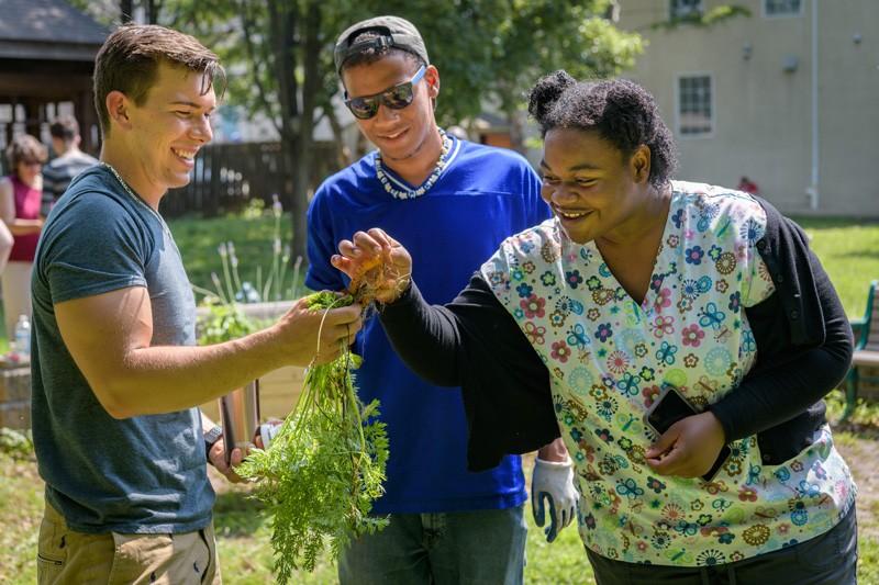Students (from left) Nicholas Matt, Jordan Watson and Ifunanya Ugorji check out a carrot from the garden.