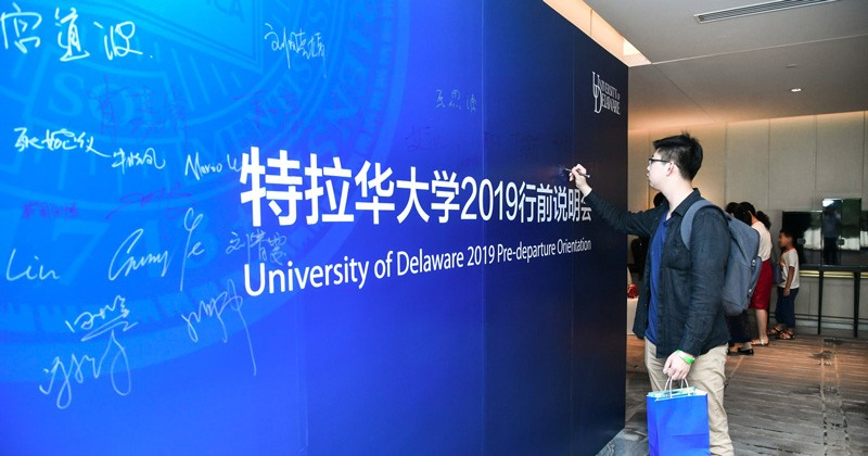 Incoming Chinese students like Chen Yiyang renewed their commitment to attending UD by signing the big blue board at the pre-departure orientation in Beijing.
