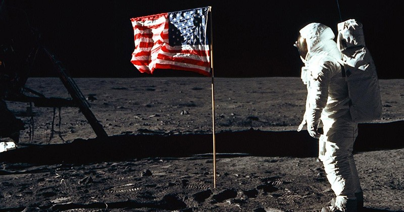 Astronaut Edwin E. Aldrin Jr., lunar module pilot of the first lunar landing mission, poses for a photograph beside the deployed United States flag during an Apollo 11 extravehicular activity (EVA) on the lunar surface. The Lunar Module (LM) is on the left, and the footprints of the astronauts are clearly visible.