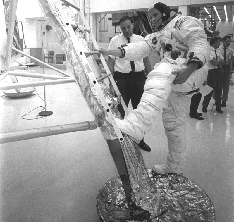 In preparation of the nation's first lunar landing mission, Apollo 11 crew members underwent training to practice activities they would be performing during the mission. In this photograph, Neil Armstrong, in his space suit, practices getting back to the first rung of the ladder on the Lunar Module.