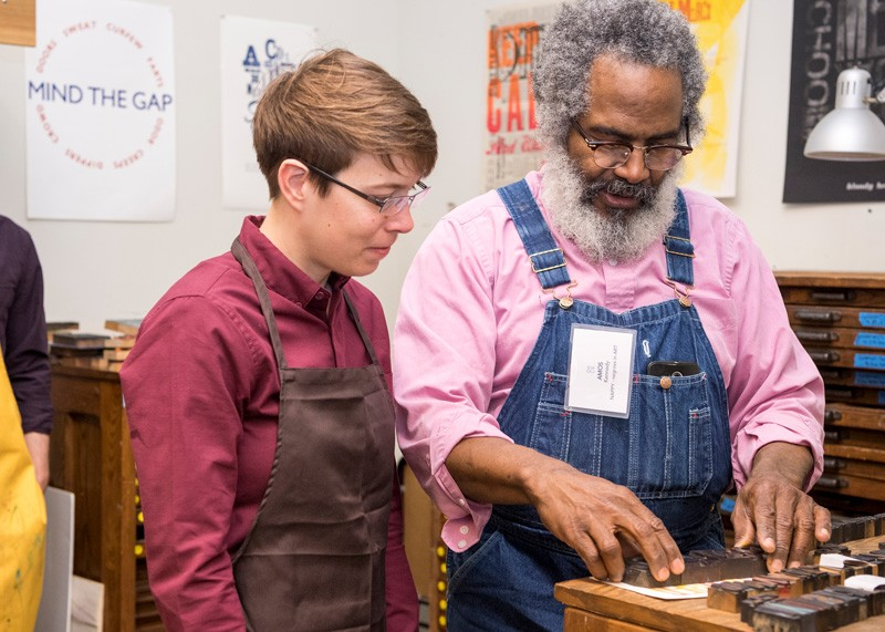 Heidi Morse (left) watches workshop leader Amos Kennedy Jr. set letterpress type. Morse, a lecturer in the University of Michigan's Department of Afroamerican and African Studies, attended the symposium and the earlier workshop at UD.