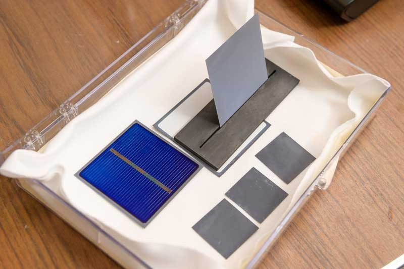 This device holds a wafer at a 60-degree angle, allowing scientists to treat both sides of a silicon wafer simultaneously. The blue wafer shows the front surface of a solar cell with fine metal grids and a bus bar for electrical contact. The blue color comes from a thin layer (80 nanometers) of amorphous silicon nitride film that protects the silicon surface and provides anti-reflection properties for the solar cell.