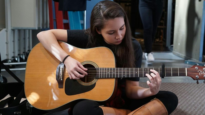 UD student Bailey Weatherbee  playing the guitar backstage during the 2017 Filipino Student Association Culture Night.