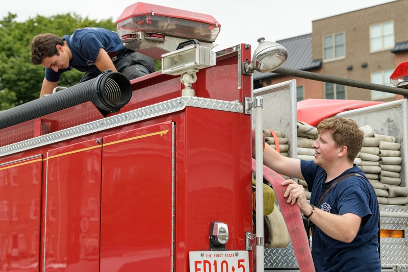 Matthew Heebner (left) and Connor Sproat (right) check equipment on the truck during some downtime at the station.