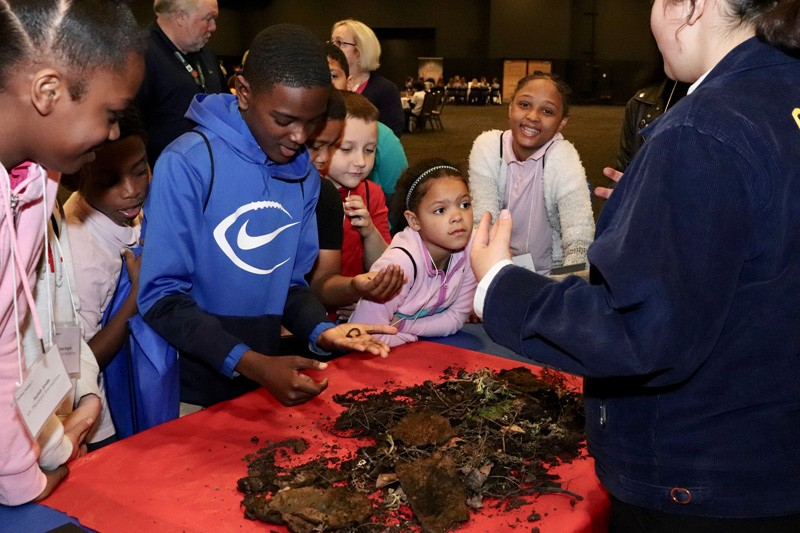 Children look for worms in the compost pile while learning about fruit and vegetable production at the third annual Delaware children's hunger conference.