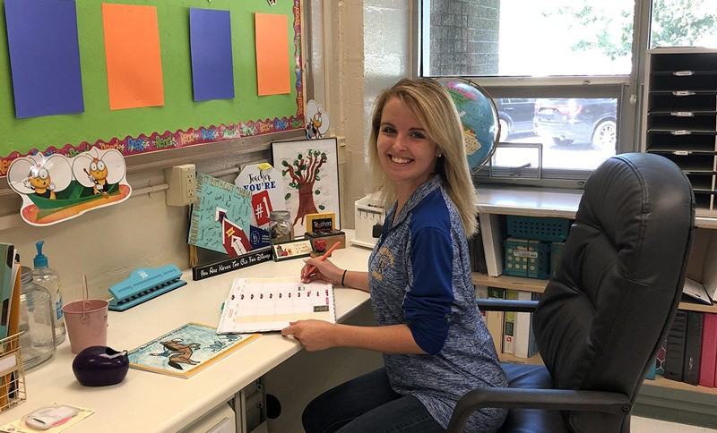 Emily Halliday, who earned her UD Associate in Arts degree in Elementary Teacher Education in Georgetown in 2016, and her bachelor's degree in education two years later on the Newark campus, sits at her desk in Welch Elementary School in Dover, where she teaches second grade special education.