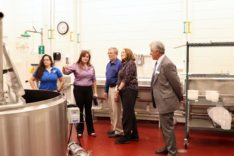 Dairy Plant Manager Jennifer Rodammer (second from left) gives tour to guests at the recent unveiling ceremony.