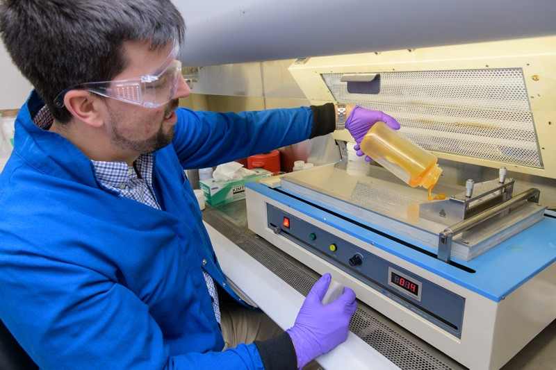 Jared Nash, chemical engineer, pours W7energy's novel polymer onto a membrane caster in order to produce the startup company's unique PiperION membranes for fuel cell applications.