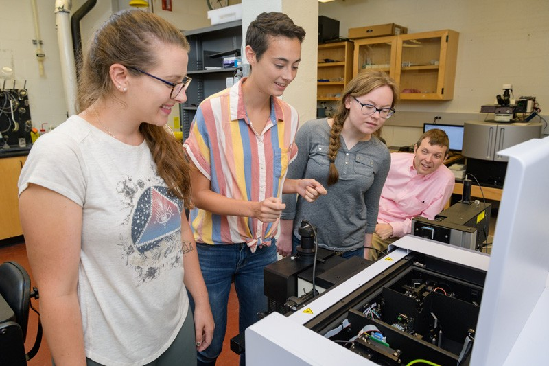Rachel McCormick (second from left) gives fellow doctoral student Devon Haugh (left) and Wofford College undergrad Savannah Talledo some training in how to use the new microscope, as Prof. Karl Booksh looks on.