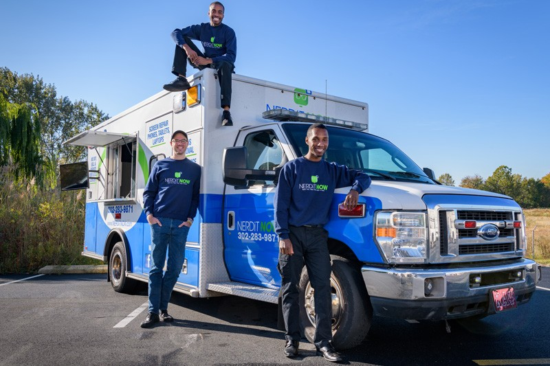 Business partners Markevis Gideon (atop vehicle), Jonathan Hoxter (right) and Jake Voorhees will appear on ABC Television's Shark Tank on Sunday, Oct. 27. Their tech company NerdiT Now repairs electronics, picking up and dropping off the items in a retrofitted ambulance.