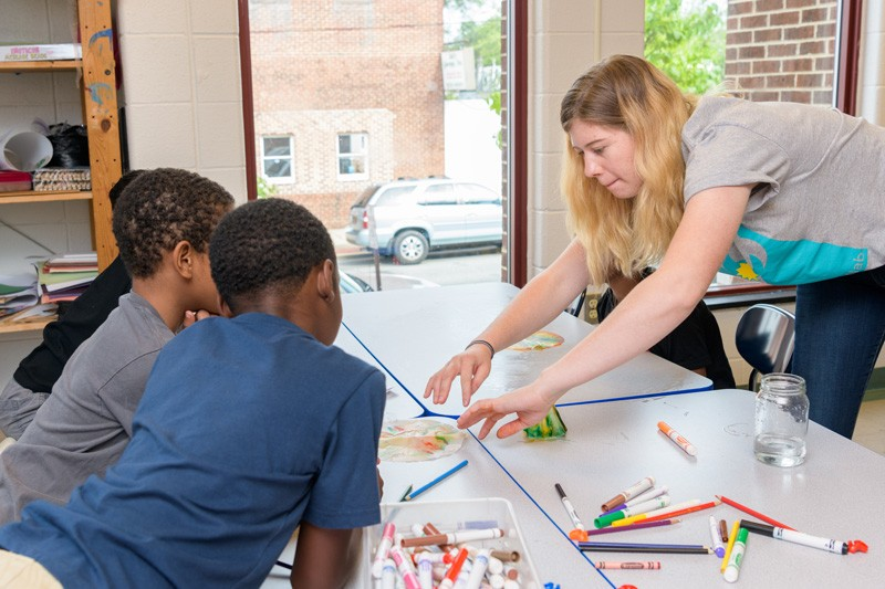 UD student River Shannon supervises youngsters at West End Neighborhood House in a project in which they use markers to draw patterns on coffee filters and then observe what happens when the filter absorbs water.