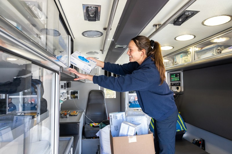Elizabeth deBruin, an EMT and a student at UD, loads PPE items donated by the University of Delaware into an Aetna ambulance.