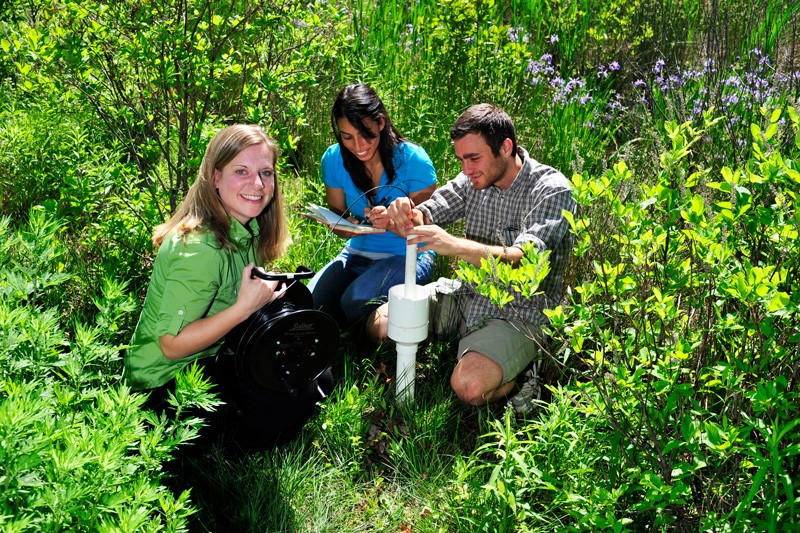 In a photo taken before the social distancing requirement necessitated by the coronavirus (COVID-19) pandemic, Holly Michael (left), acting director for environmental issues with the Delaware Environmental Institute, works in a small marsh situated on University of Delaware's East Campus, near Perkins Students Center.