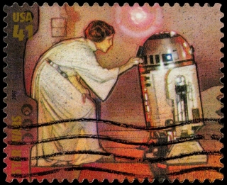 A 2007 U.S. postage stamp with an illustration of Star Wars characters Princess Leia Organa Solo (with visible right-side bun) and astromech droid R2-D2. The illustration shows a well-known scene from the first Star Wars movie in which a hologram of Leia is projected out of R2-D2.""