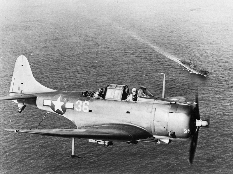 Close-up of an SBD Dauntless flying over the USS Enterprise.