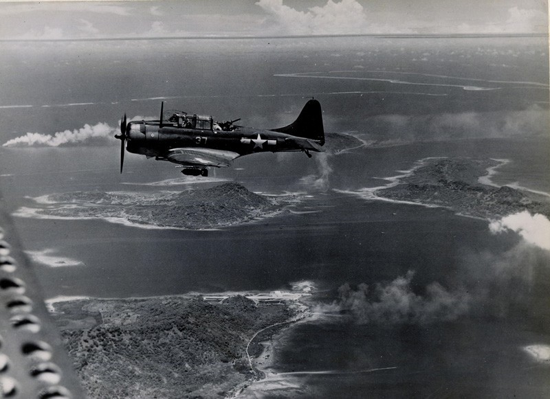 SBD Dauntless seeking targets over Truk Lagoon as fires rage among the islands below.