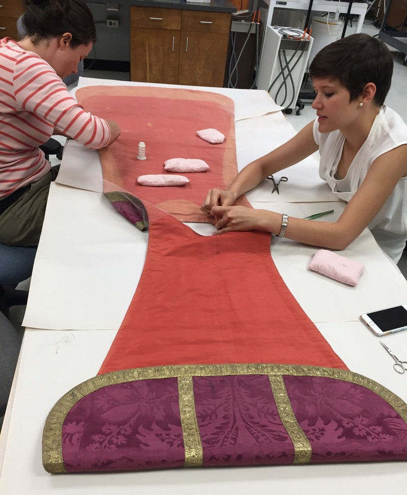 Annabelle Camp (right), an art conservation student specializing in textiles, helps stabilize a Catholic vestment from Mission San Xavier del Bac during an internship at the Arizona State Museum.