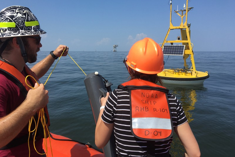 Scientists from NOAA's Cooperative Institute for Marine and Atmospheric Studies (CIMAS) prepare to collect a water sample near an ocean acidification buoy in the Gulf of Mexico with an oil platform in the background.