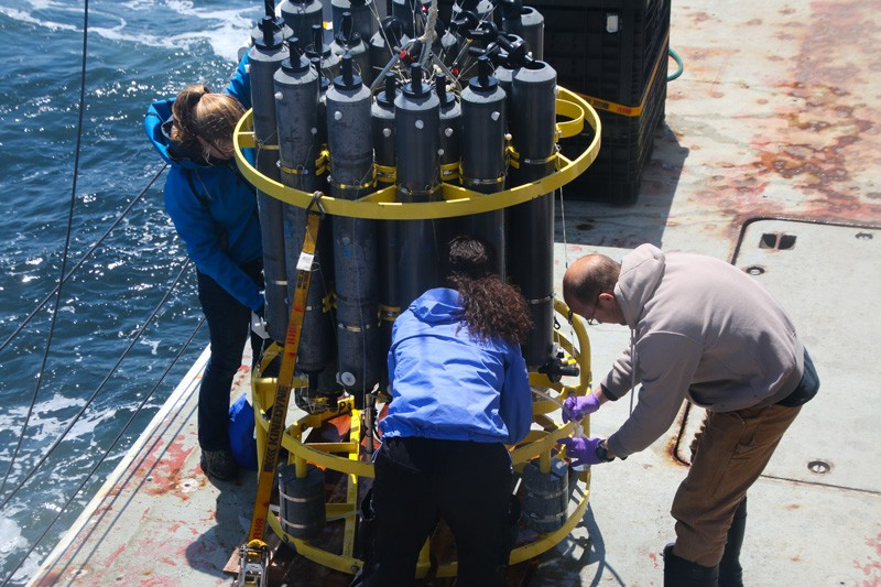 Scientists gather around a Conductivity, Temperature, Depth (CTD) rosette, a machine used during the West Coast Ocean Acidification Cruise, to collect samples that measure concentrations of oxygen, pH, and carbon, salinity, chlorophyll and nutrients.