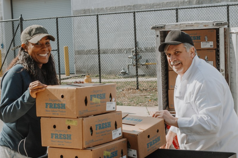 Sharee Dorsett (left), co-pastor of Wilmington's City of Love Church, receives a donation of food from UD's catering executive chef, Carl Zampini. The vegetables and other items fed around 500 families in two-and-a-half days.