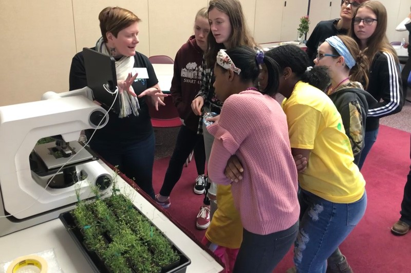 UD Prof. Erin Sparks explains a plant experiment to middle school students at the STEM event on the Delaware Tech campus in Georgetown.