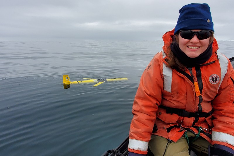 Katherine Hudson, a UD doctoral candidate and a Patricia and Charles Robertson Fellow, conducting research in Antarctica with the Slocum Glider, one of UD's Autonomous Underwater Vehicles, in the background.