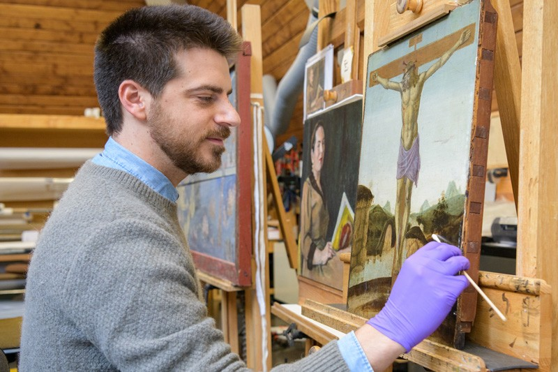 Isaac Messina surface cleans a late 15th-century Italian panel painting from Bryn Mawr College in the painting conservation studio at Winterthur.