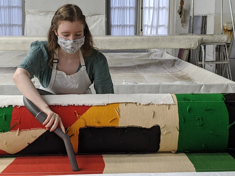 Miriam-Helene Rudd, a senior art conservation major, pictured here cleaning a tapestry