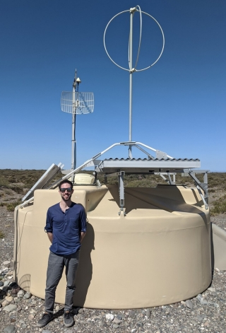 Alan Coleman stands by one of the Pierre Auger Observatory's 1,600 cosmic ray detector station
