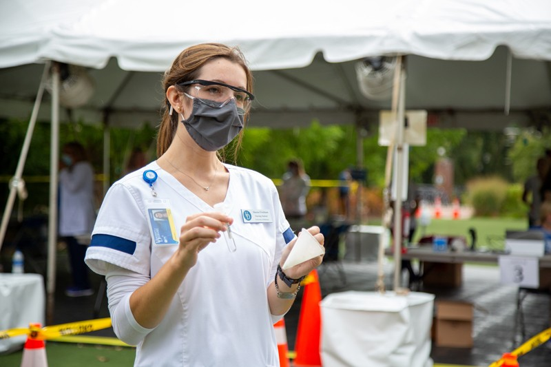 UD senior nursing student Shaena Friedman demonstrates how to collect the saliva sample for the coronavirus (COVID-19) surveillance testing. Friedman said the testing is a way for students like her to get experience in a community health setting.