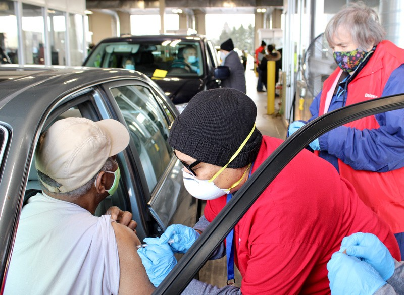 Delaware Medical Reserve Corps volunteer Veronica Scott Holmes administers a COVID-19 vaccination during a recent drive-thru event in Delaware City. Nursing emerita Evelyn Hayes, also a member of the DMRC, is in the background.