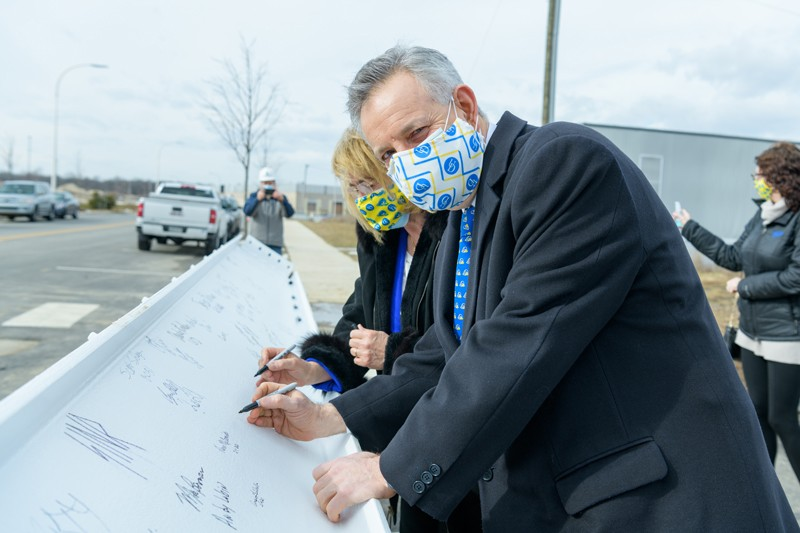 University of Delaware President Dennis Assanis and his wife, Eleni, were among those who signed the final beam of the FinTech Innovation Hub.