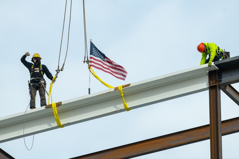 Workers guide the final beam into place on Wednesday, Feb. 10, marking the halfway point of construction on the FinTech Innovation Hub on UD's STAR Campus.